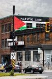 A bandeira de Palestina e o slogan livre do libre de Palestina Palestina pintaram nas paredes de tijolo de uma construção em Mont foto de stock