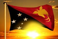 Bandeira de Papuásia-Nova Guiné que tece no por do sol alaranjado bonito com fundo das nuvens fotos de stock