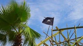 A bandeira de pirata esfarrapada rasgada acena no vento amarrado ao equipamento no navio alto Dewarcuci enquanto as nuvens passam filme
