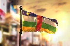 Bandeira de República Centro-Africana contra o fundo borrado cidade em Fotos de Stock