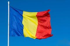 Bandeira de Romênia no cargo que move-se no vento Bandeira vermelha, verde e azul romena que acena no vento com fundo azul claro fotografia de stock