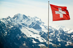 A bandeira de Suíça nas montanhas dos cumes ajardina o fundo Foto de Stock Royalty Free