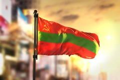 Bandeira de Transnistria contra o fundo borrado cidade no CCB do nascer do sol Foto de Stock Royalty Free