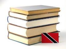 Bandeira de Trindade e Tobago com a pilha dos livros isolados nos vagabundos brancos Fotografia de Stock