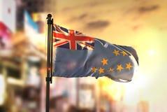 Bandeira de Tuvalu contra o fundo borrado cidade no luminoso do nascer do sol Imagem de Stock Royalty Free