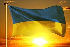 Bandeira de Ucrânia que tece no por do sol alaranjado bonito com fundo das nuvens imagens de stock