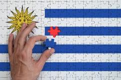 A bandeira de Uruguai é descrita em um enigma, que a mão do ` s do homem termine para dobrar imagem de stock