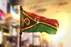 Bandeira de Vanuatu contra o fundo borrado cidade no nascer do sol Backligh Foto de Stock Royalty Free