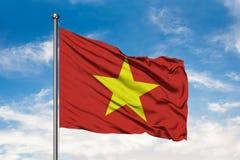 Bandeira de Vietname que acena no vento contra o céu azul nebuloso branco Bandeira vietnamiana fotografia de stock royalty free