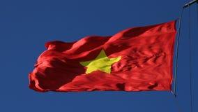Bandeira de Vietname que funde no vento duro contra o céu azul claro filme