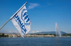 Bandeira do alto comissário de United Nations para os refugiados (UNHCR) que acenam no vento no lago geneva imagens de stock