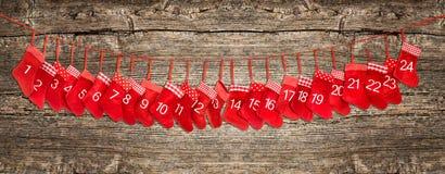 Bandeira do calendário do advento Natal vermelho que armazena o fundo de madeira Fotos de Stock