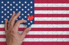 A bandeira do Estados Unidos da América é descrita em um enigma, que a mão do ` s do homem termine para dobrar imagem de stock