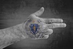 Bandeira do selo de Massachusette do estado de E.U. pintada na mão masculina como uma arma foto de stock royalty free