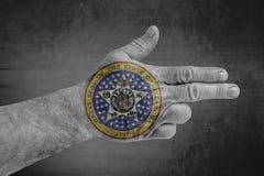 Bandeira do selo do estado de Oklahoma pintada na mão masculina como uma arma imagem de stock royalty free