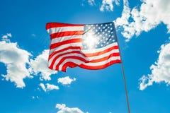 Bandeira dos E.U. com nuvens de cúmulo e o céu azul no fundo imagens de stock
