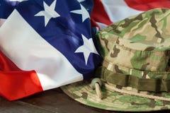 Bandeira dos E.U. com o chapéu do combate da camuflagem Fotografia de Stock