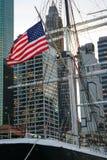 Bandeira dos E.U. em um barco de três mastros com os skyscrappers de Manhattan como o CCB Imagem de Stock