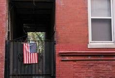 Bandeira dos E.U. vista unida a uma porta lateral em uns E.U. em casa fotos de stock