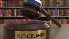 Bandeira dos Países Baixos no martelo de queda dos juizes no tribunal Justiça ou a jurisdição nacional relacionaram 3D conceptual video estoque