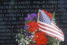 Bandeira e flores na frente do memorial da parede de Vietname, Washington, D C Fotografia de Stock