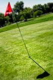 Bandeira e furo no campo do golfe Imagens de Stock