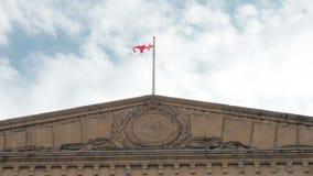A bandeira Georgian vibra no vento na parte superior da construção do governo contra o céu filme