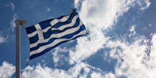 Bandeira grega no mastro de bandeira que acena no fundo do céu azul foto de stock