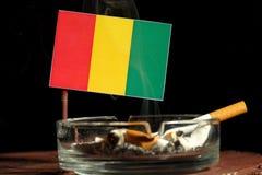 Bandeira guineense com o cigarro ardente no cinzeiro no preto Fotografia de Stock