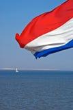 Bandeira holandesa com o navio de navigação pequeno no fundo foto de stock royalty free