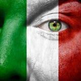 A bandeira italiana pintada sobre equipa a cara Fotos de Stock