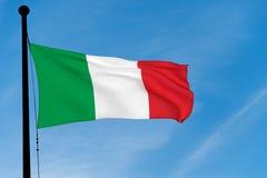 Bandeira italiana que acena sobre o céu azul Fotografia de Stock Royalty Free