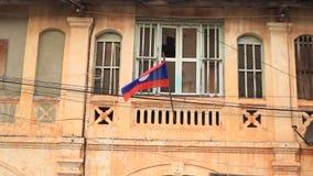 Bandeira Laotian que pendura de uma casa comunista de deterioração do estilo em Suvannakhet filme