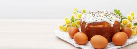 Bandeira larga com bolo da P?scoa e as flores amarelas coloridas da flor dos ovos no fundo Alimento do feriado e conceito de east imagem de stock