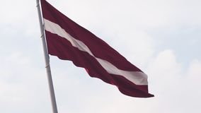 Bandeira letão que vibra na elevação do vento acima no céu durante um por do sol dourado da hora - capital de Riga, Letónia - Dam vídeos de arquivo