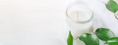 Bandeira longa para a vela branca do bem-estar orgânico dos cosméticos em ramos de árvore frescos do frasco de vidro com as folha fotos de stock