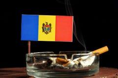 Bandeira moldava com o cigarro ardente no cinzeiro isolado no preto Imagem de Stock Royalty Free