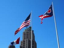 A bandeira municipal de Cleveland, Ohio, a bandeira dos E.U., & o estado de bandeiras de Ohio voam sobre Cleveland no sol do meio Fotografia de Stock Royalty Free