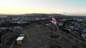 Bandeira na cidade de Gori da montanha no voo do zangão da pátria 4K de Georgia Stalin filme