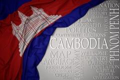 Bandeira nacional colorida de ondulação de cambodia em um fundo cinzento com palavras importantes sobre o país imagem de stock royalty free