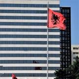A bandeira nacional de Albânia contra o contexto de um hotel super-moderno na capital Tirana fotografia de stock