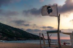 A bandeira nacional de Córsega em uma praia no por do sol Imagens de Stock Royalty Free