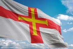 Bandeira nacional de Guernsey que acena a ilustração 3d realística do fundo do céu azul ilustração do vetor
