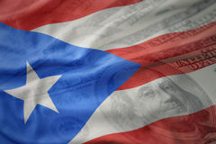Bandeira nacional de ondulação colorida de Puerto Rico em um fundo americano do dinheiro do dólar Fotografia de Stock