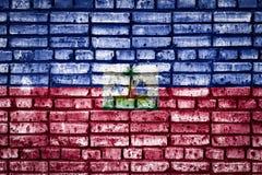 Bandeira nacional em um fundo do tijolo fotografia de stock