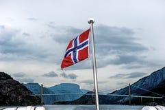 Bandeira norueguesa no fundo da ponte e do fiorde cercados por montanhas Fotos de Stock