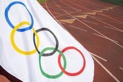 Bandeira olímpica que acena na pista de atletismo foto de stock royalty free