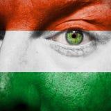 Bandeira pintada na cara com olho verde para mostrar o apoio de Hungria Fotos de Stock Royalty Free