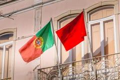 Bandeira portuguesa e bandeira do partido comunista em uma fachada da construção fotografia de stock