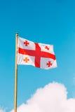 Bandeira próxima de Georgia Five Cross Flag Waving em Sunny Sky Background azul Fotos de Stock